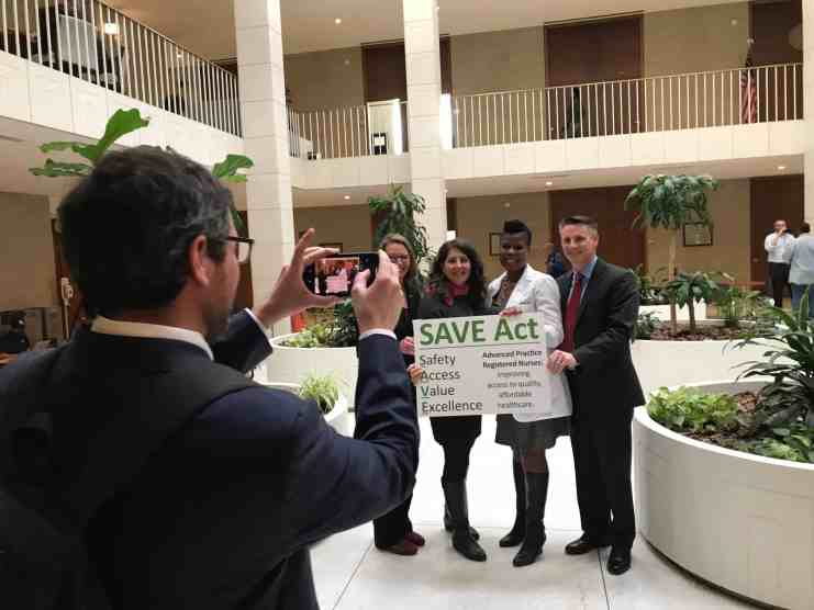 """a man takes a picture of four people on his phone, they're holding a sign that says """"SAVE Act"""""""