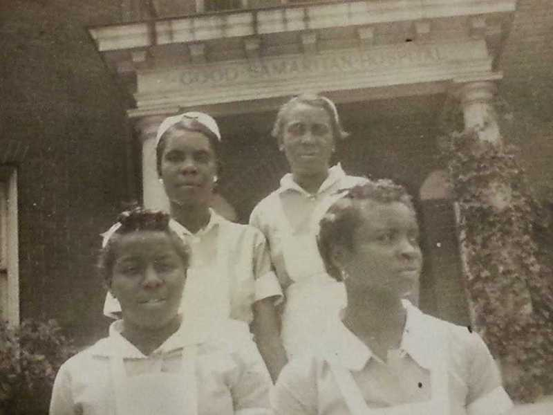 """Four women in white nurses uniforms and caps in front of a brick building which says """"GOOD SAMARITAN HOSPITAL"""""""