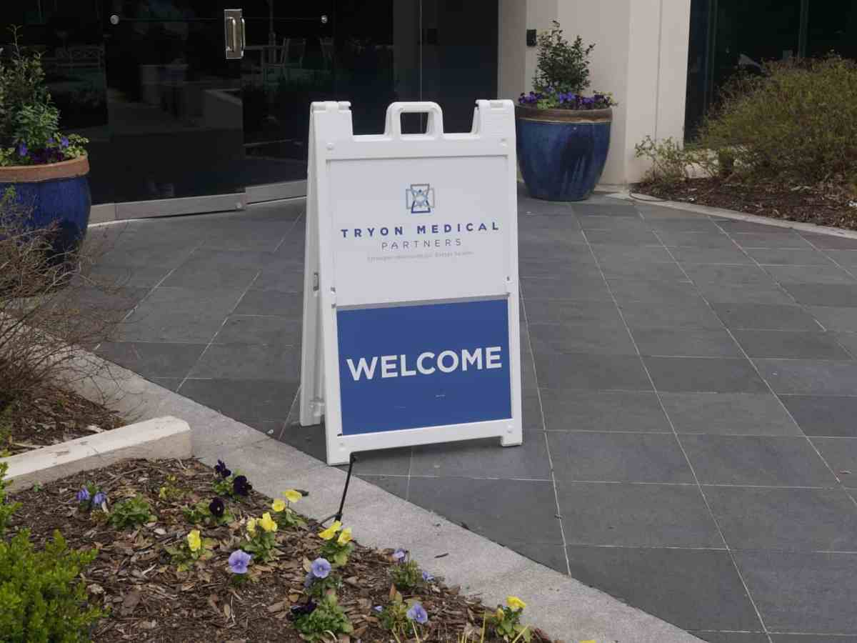 """A pop up plastic sign on a sidewalk which reads """"welcome"""""""