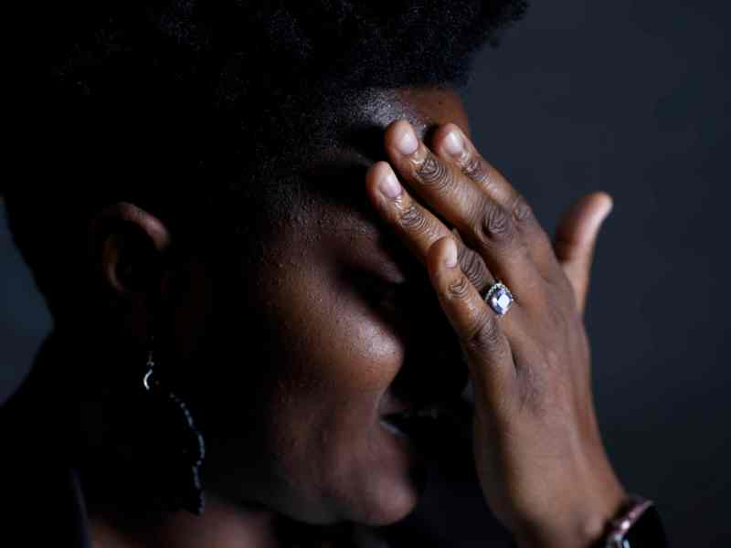 shows a woman with her hand over her face in sadness and frustration. much of her face is in shadow.