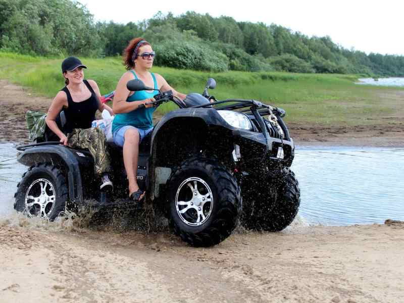 shows two women without helmets on an ATV, driving through water.