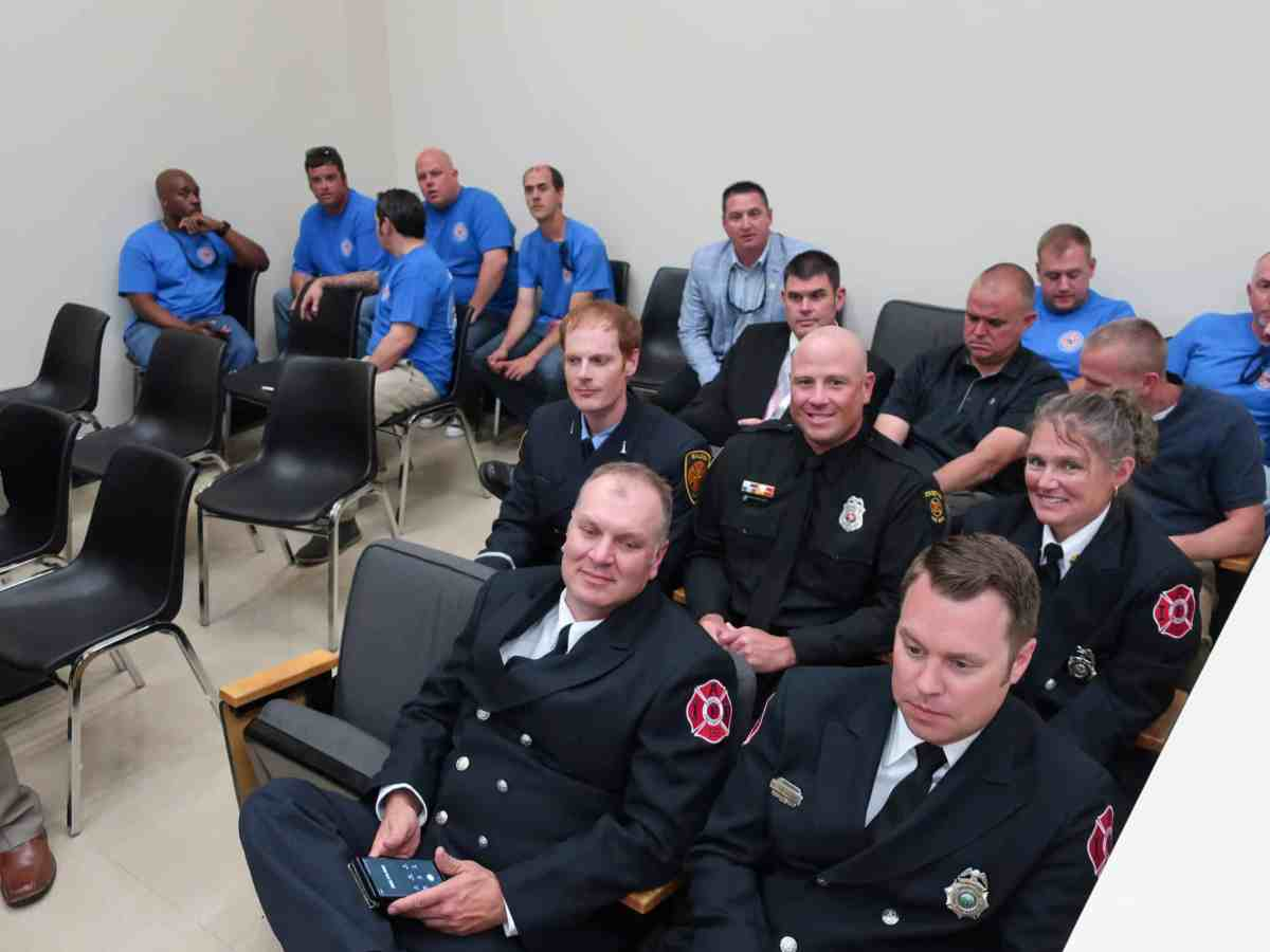 shows a group of men and women in uniform, sitting in chairs in a room