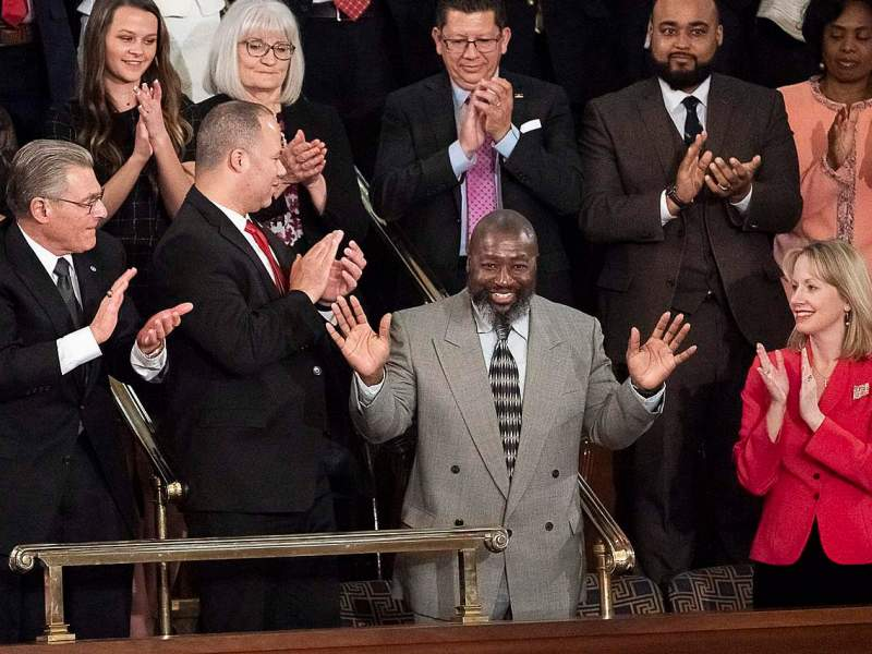 shows an african american man standing as standing people around him applaud