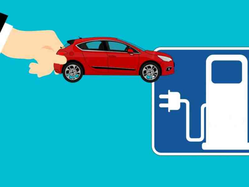 cartoon image of a hand plugging a car into an electric charging station sign