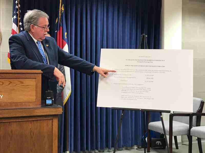 Man stands at a podium, points at an easel with a display on it, explaining his Medicaid expansion plan