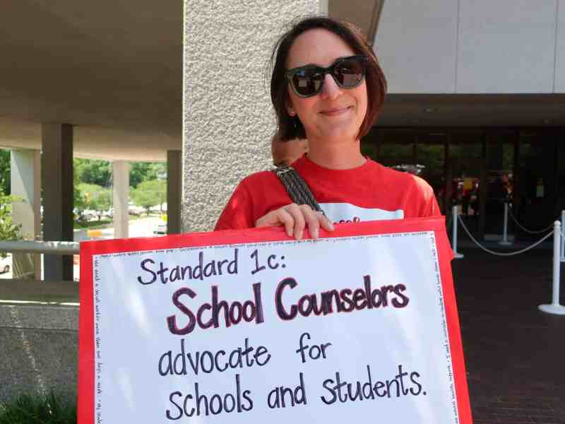 """A woman in red holds up a sign reading: """"Standard 1.C School Counselors advocate for students and schools"""""""