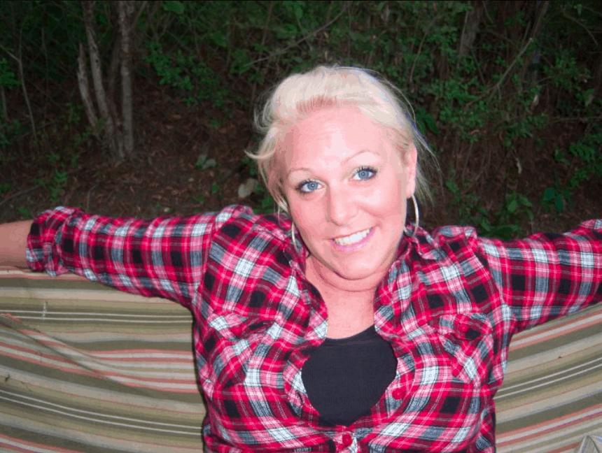 shows a smiling young woman wearing a plaid shirt, similing at the camera
