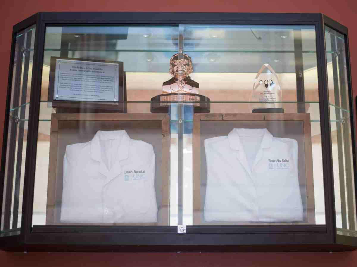 shows a glass case with Deah and Yusor's white jackets