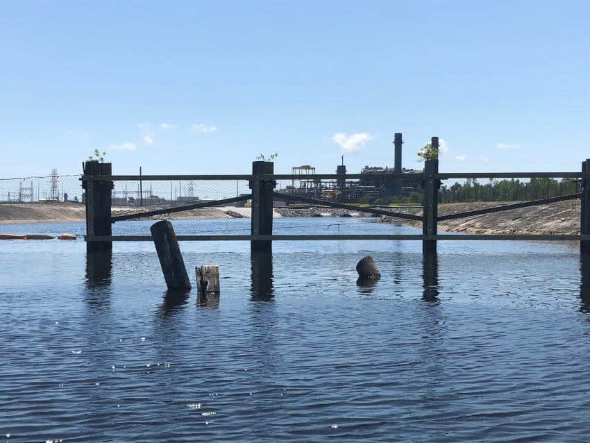 shows a lake with pilings sticking up from the water. It's a lake contaminated with coal ash.
