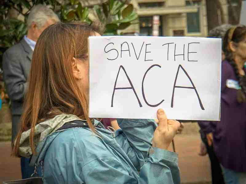 """Woman holds up a sign reading, """"Save the Affordable Care Act"""""""