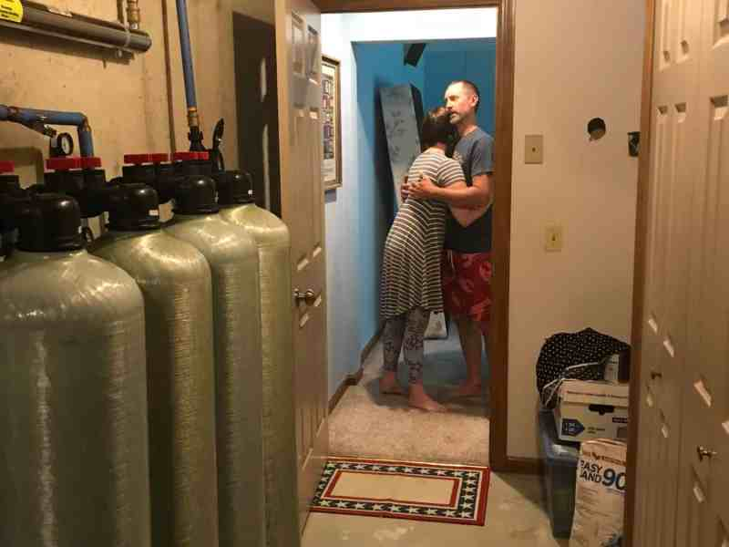 shows a couple embracing in a room, in the foreground are the tanks of the water filtration system.