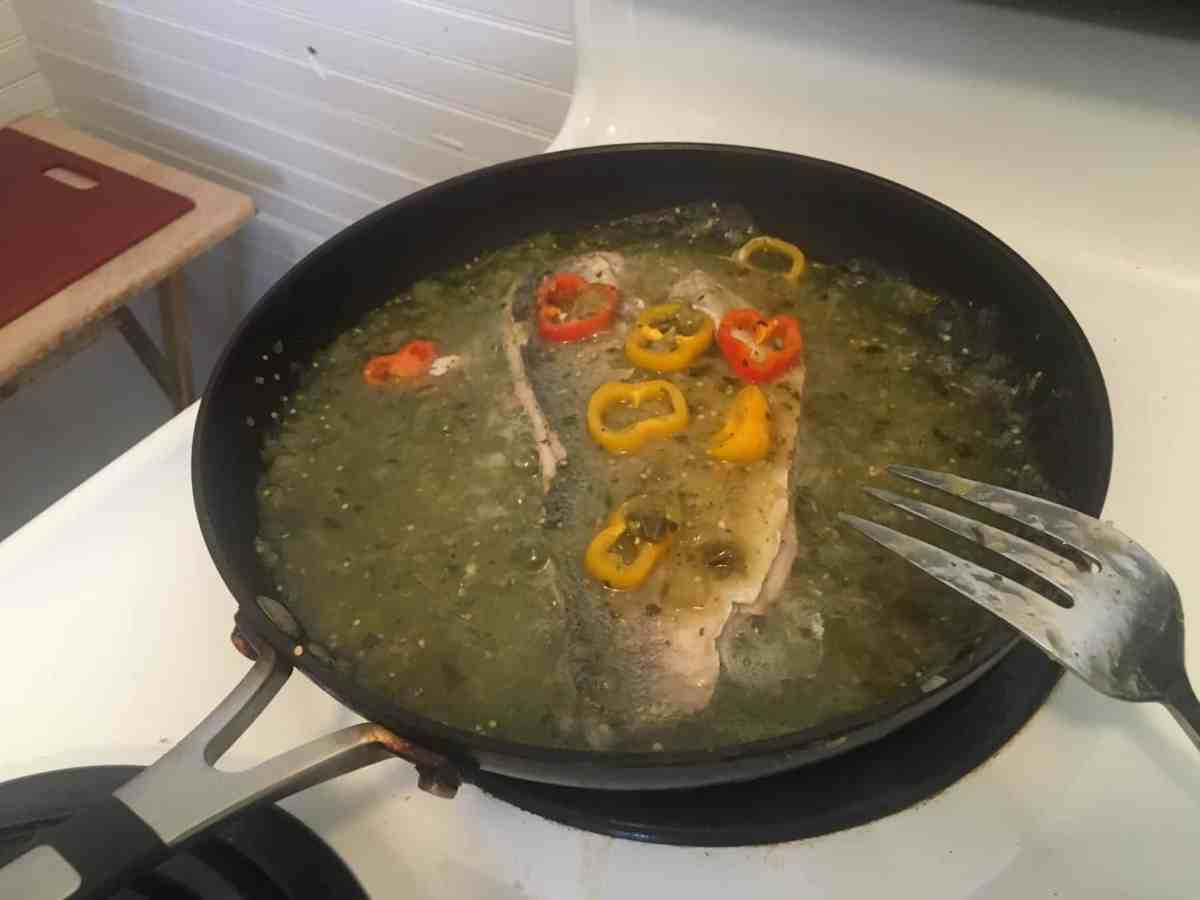 Mediterranean food design (!) and cooking by TRG, shows a fish being braised in a pan with red and yellow peppers