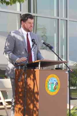 A man in a gray suit and red tie stands at a podium with two microphones in front of him.