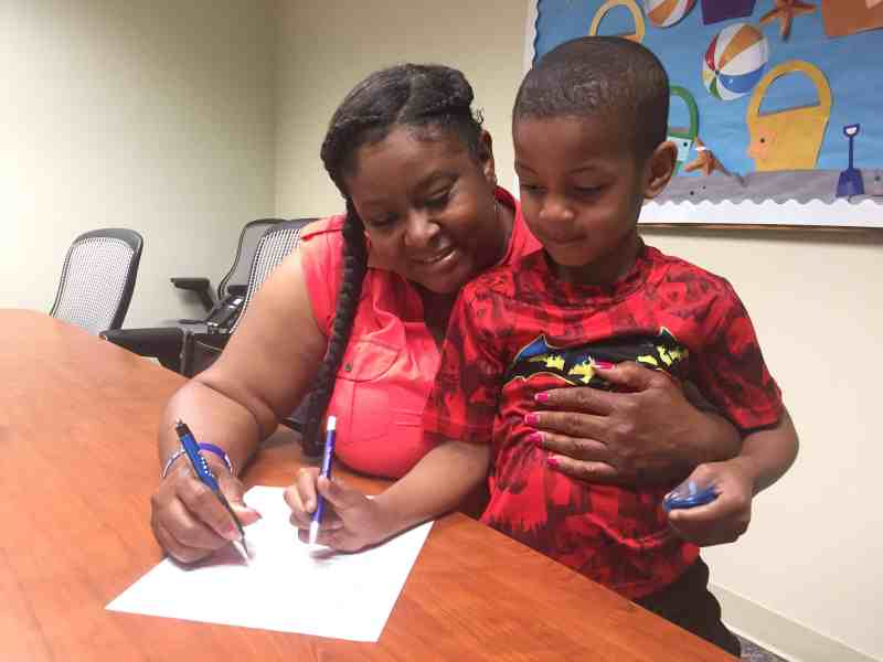 Shows a woman hugging a little boy she's had in foster care. She is signing his adoption papers.
