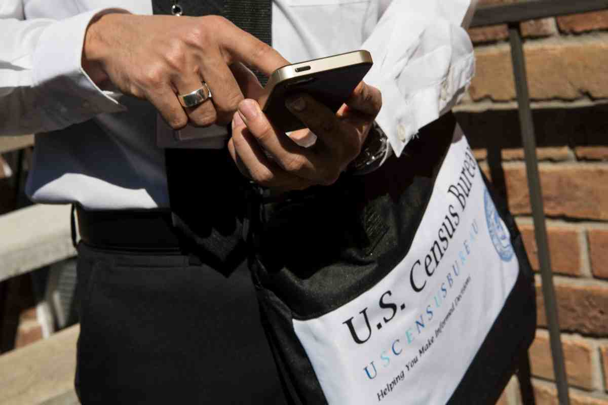 shows hands using a cell phone, the person is carrying a bag labeled US Census