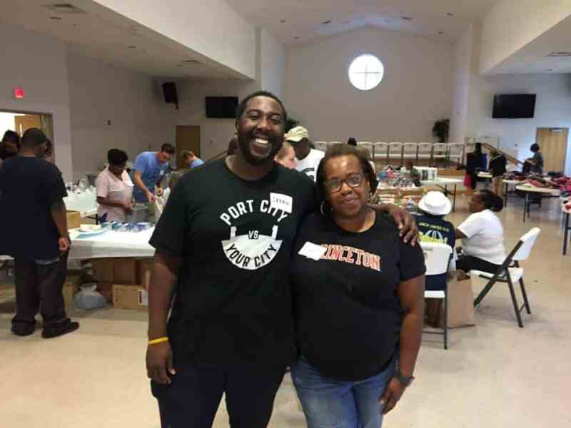 shows a smiling young man and an older woman with arms around each other, smiling at the camera, while at a disaster relief event in a Wilmington church