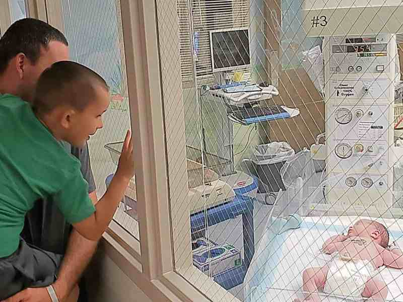 A little boy is on his dad's arm, looking at a baby through a window at Martin General Hospital, which will soon stop offering maternity services