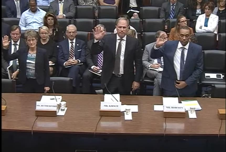 shows three people behind a table with microphones, they're each standing and raising their right hands before they testify about PFAS