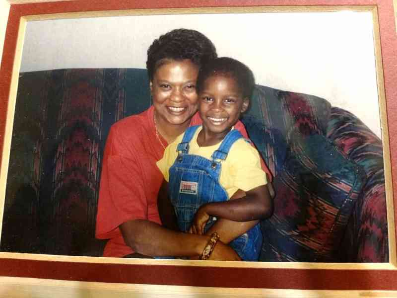Shows an old photo of a woman hugging a little boy, they're both smiling.