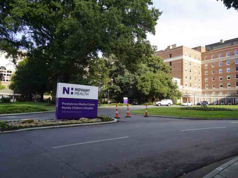 A sign for Novant Health Presbyterian Medical Center, with a large tree and the hospital in the background