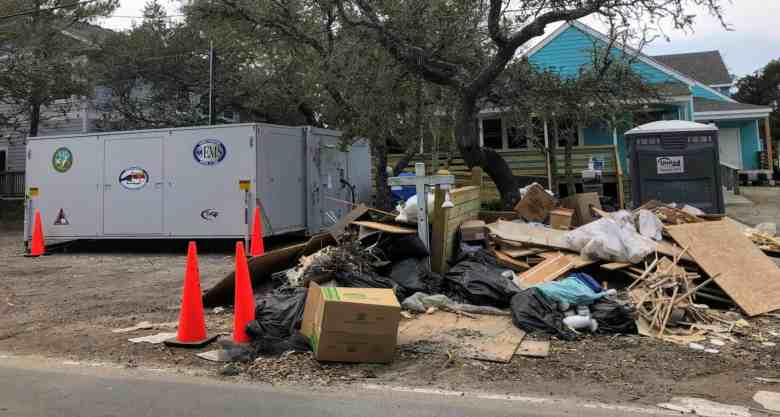 Shows a mobile clinic unit with piles of construction debris next to it.