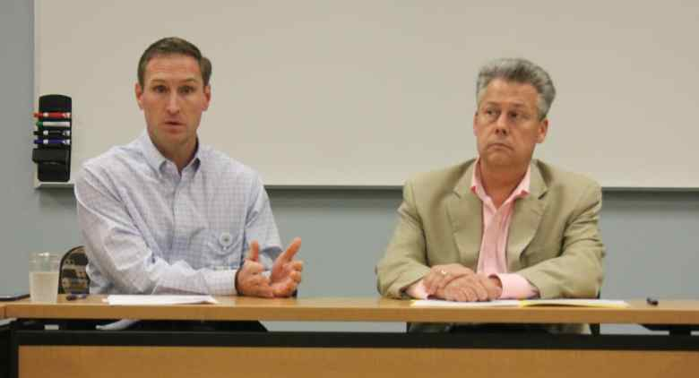 Two men are sitting in front of a table. The man in the blue shirt is talking, his hands are on the table. The man in the tan suit isn't talking. The two men are the CEO of New Hanover Regional Medical Center and the New Hanover County manager, and both are at a meeting to discuss the hospital's future.