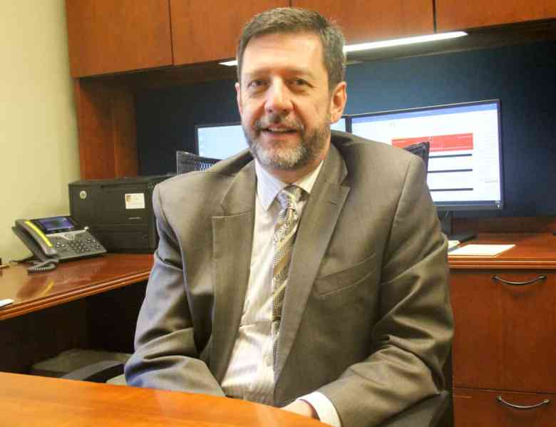 A white man in a suit sits at his office. He is Chatham Hospital CEO Jeff Strickler. His office will soon become part of hospital's the new maternity unit.