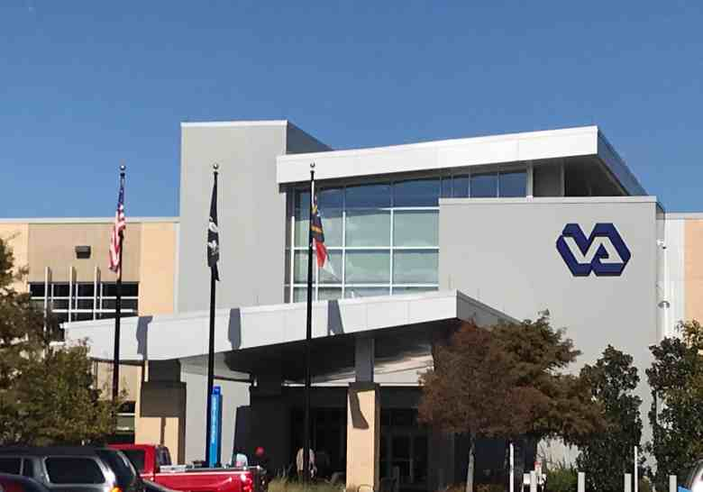 """A concrete building with the words """"VA"""" on it. This is the Veterans Affairs health center in Greenville, where there's a vet dental health clinic"""