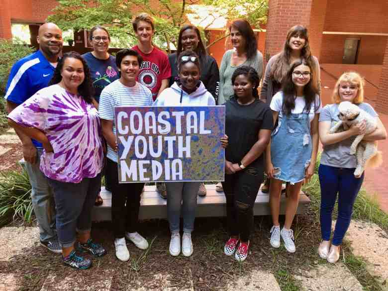 shows a group of people posing for the camera, the people in front hold a sign reading: Coastal Youth Media