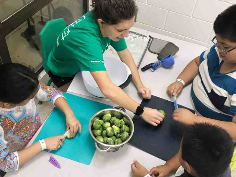 Children sitting around a table cutting greens as part of a program that tackles physical activity in Durham.