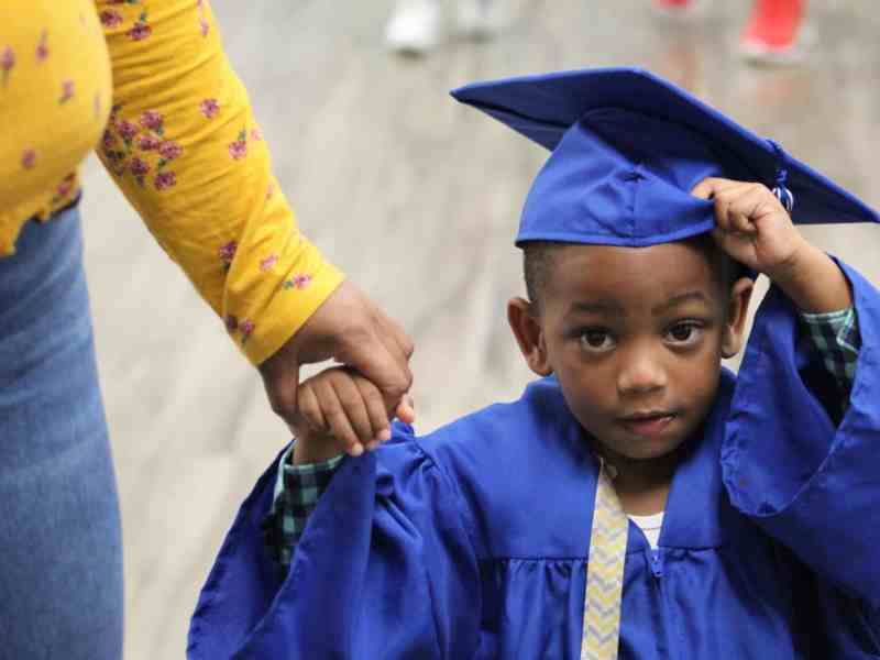 A toddler adjusting his mortarboard in a graduation gown