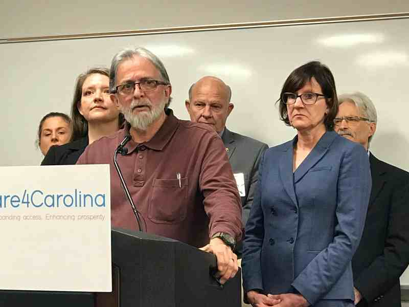 a man stands at a podium with a number of grim faced advocates for Medicaid expansion standing behind him