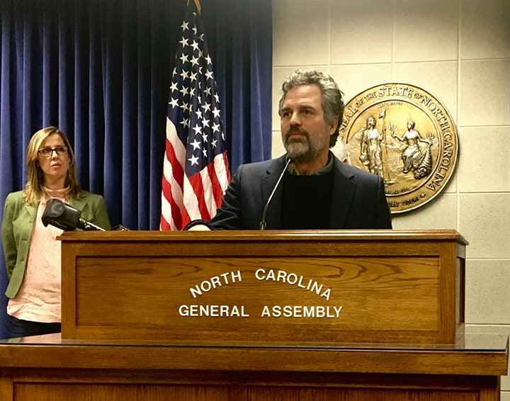 Two advocates stand at a podium addressing lawmakers last week about PFAS