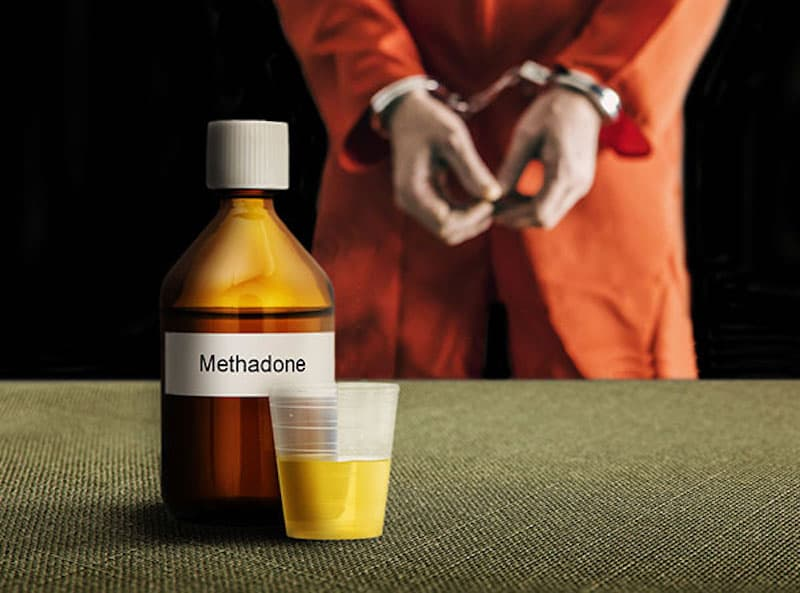 shows an inmate in a orange jail jumpsuit and handcuffs behind a bottle labeled methadone, an opioid use disorder drug that can help reduce cravings.