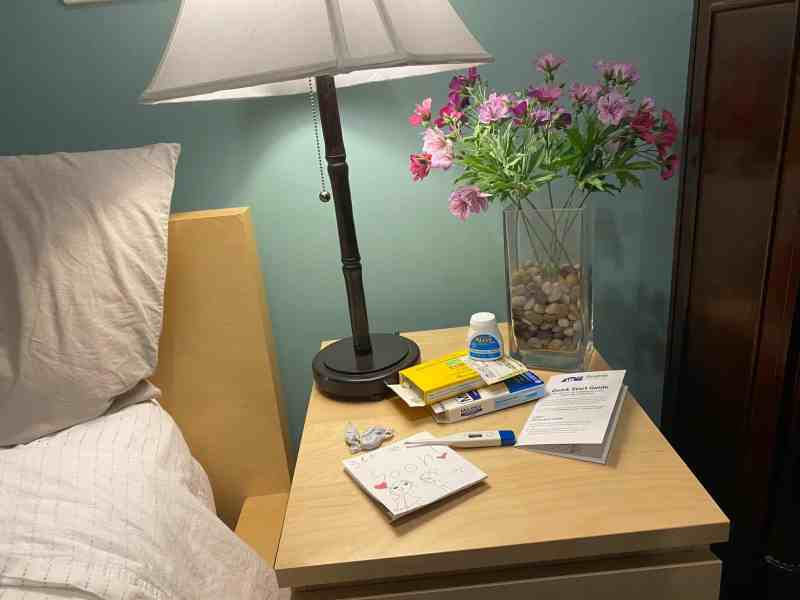shows a bedside table with a lamp and medications used during recovery from COVID-19
