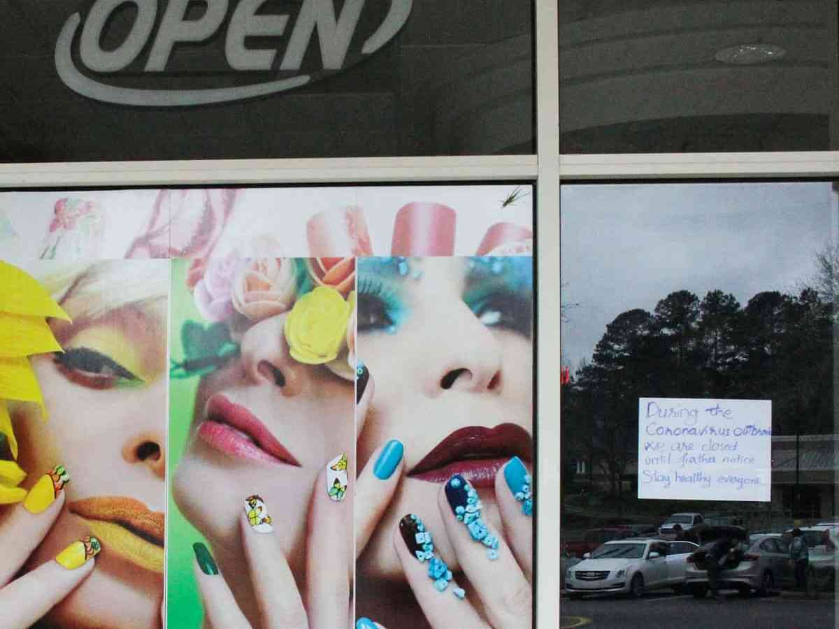 A coronavirus sign at the entrance to a closed salon says the establishment will be closed until farther notice.
