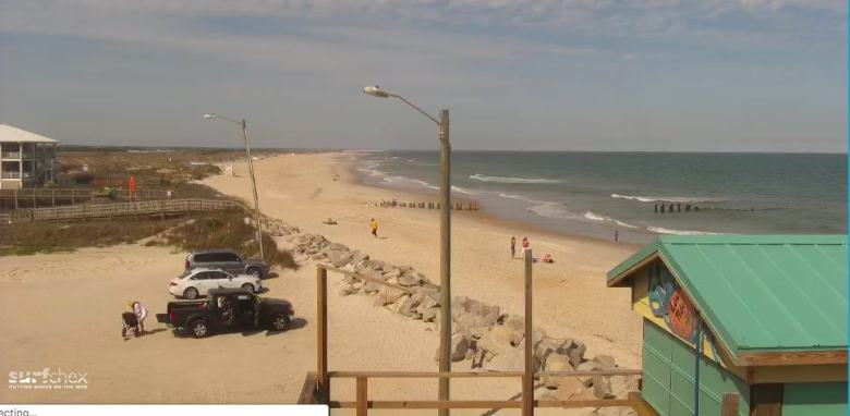 A screenshot of Carolina beach from a livestream features sands, waves and a couple of shacks