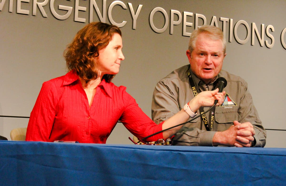 A woman holds a microphone for a man, both of them are North Carolina officials who are talking about coroanvirus at a press conference.