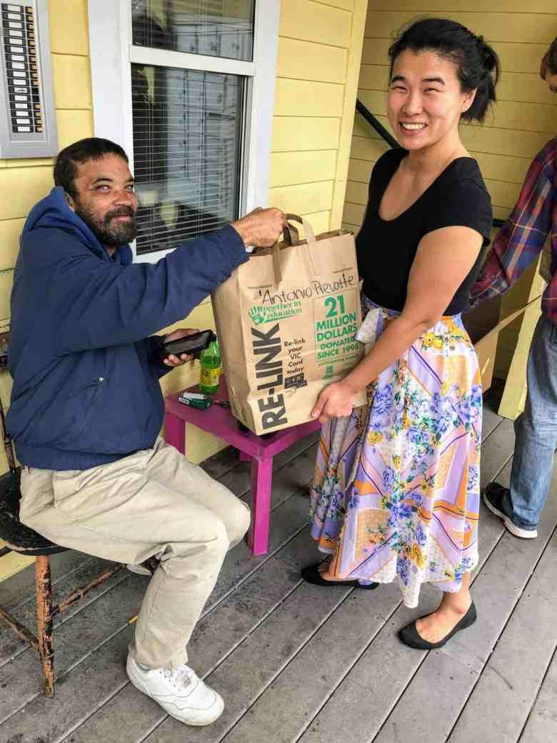 woman hands brown bag of food to man