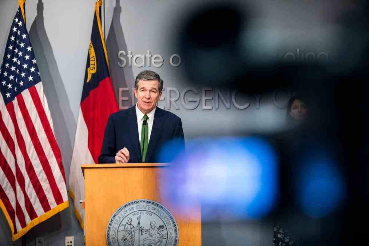Gov. Roy Cooper stands at a podium in a briefing about coronavirus. There's a video camera in the foreground.