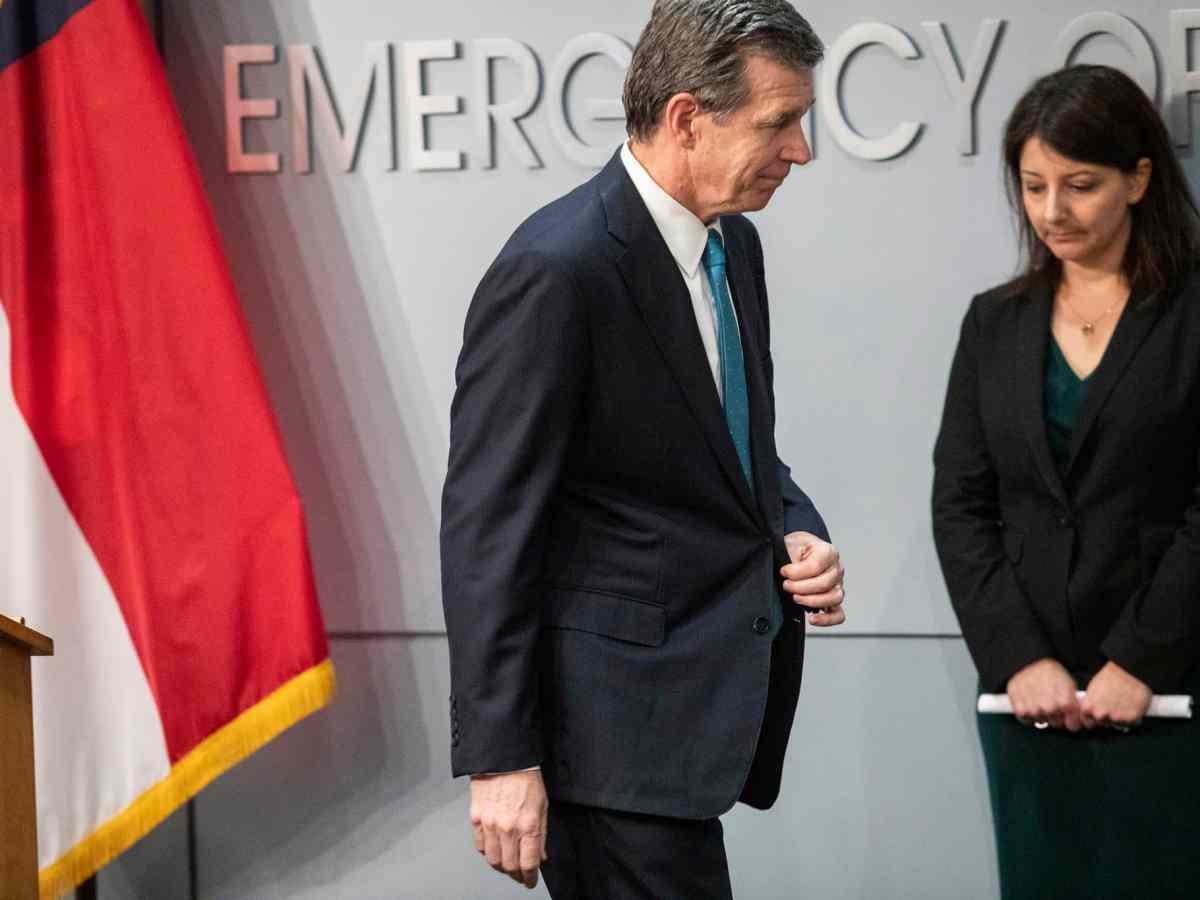 Gov. Cooper walks past Mandy Cohen at a coronavirus briefing