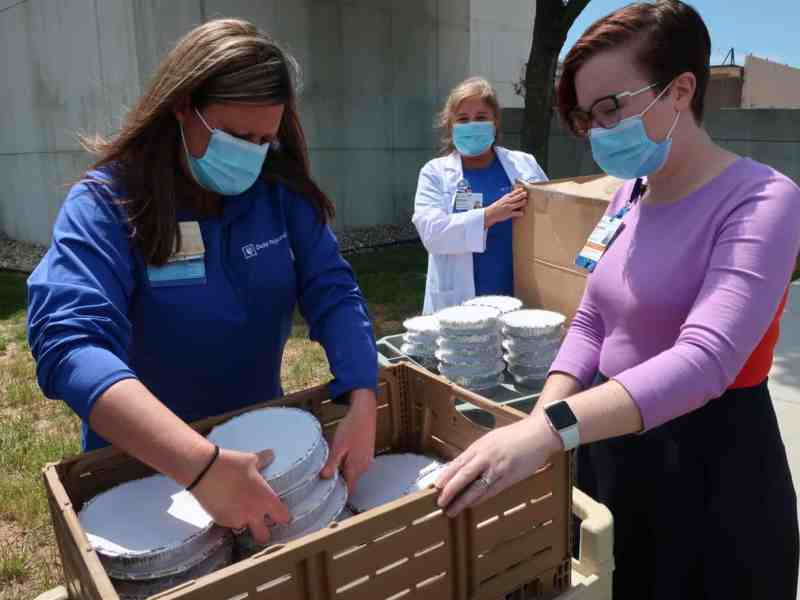 Health care professionals grab disposable takeout containers outside. Providers have been responding to the coronavirus pandemic in the state.