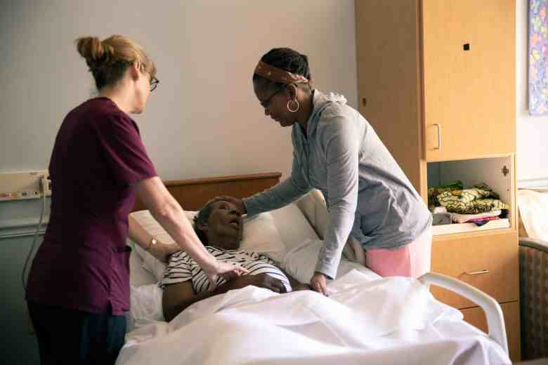 Two providers stand near a hospital bed with an African American patient. The photo was taken at a hospice facility in Wake County.