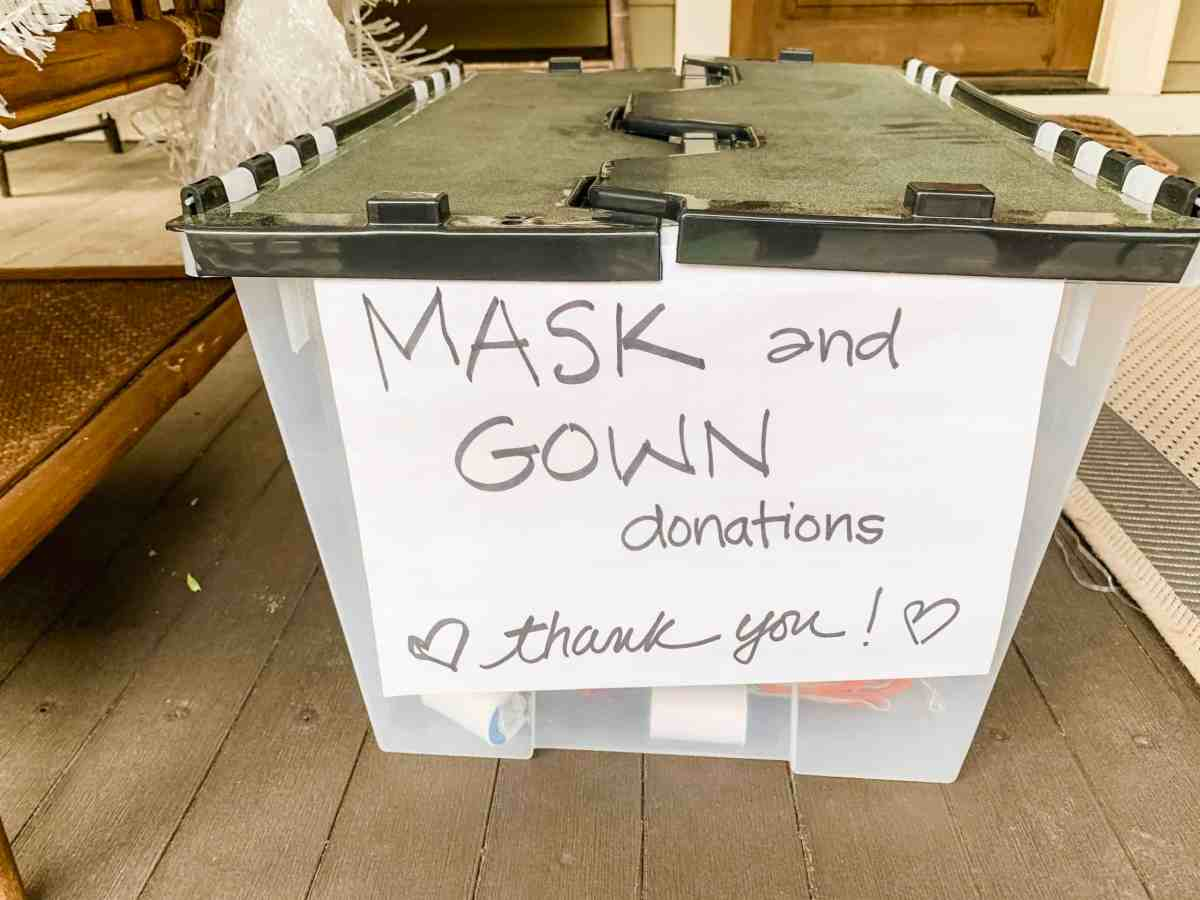 A plastic bin to collect personal protective equipment with a sign on it reading: Mask and Gown donations, Thank you!