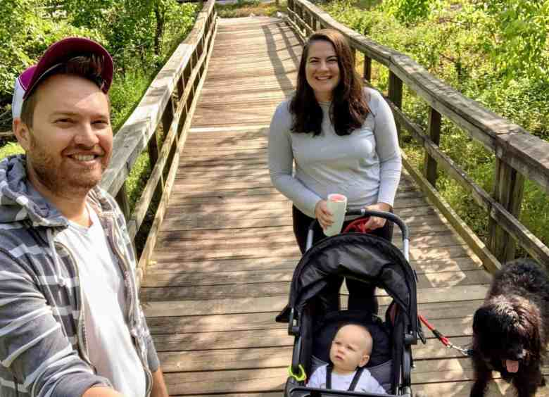 husband, wife, baby and dog on a walk to promote their mental health and helps them cope