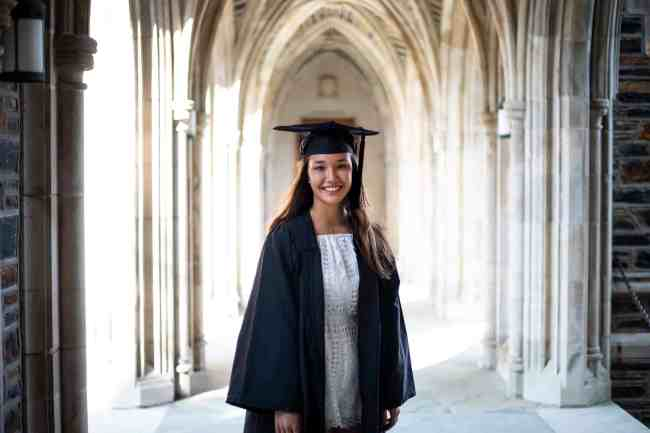 This Duke University international student earned a double major in International Comparative Studies and Religious Studies stands and smiles in her cap and gown.