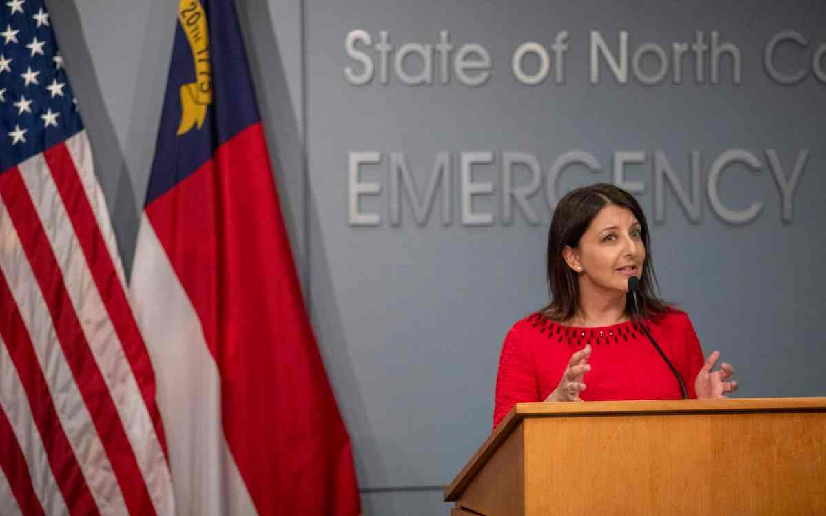 shows a woman in a red dress standing behind a podium as she talks about efforts to combat the COVID pandemic