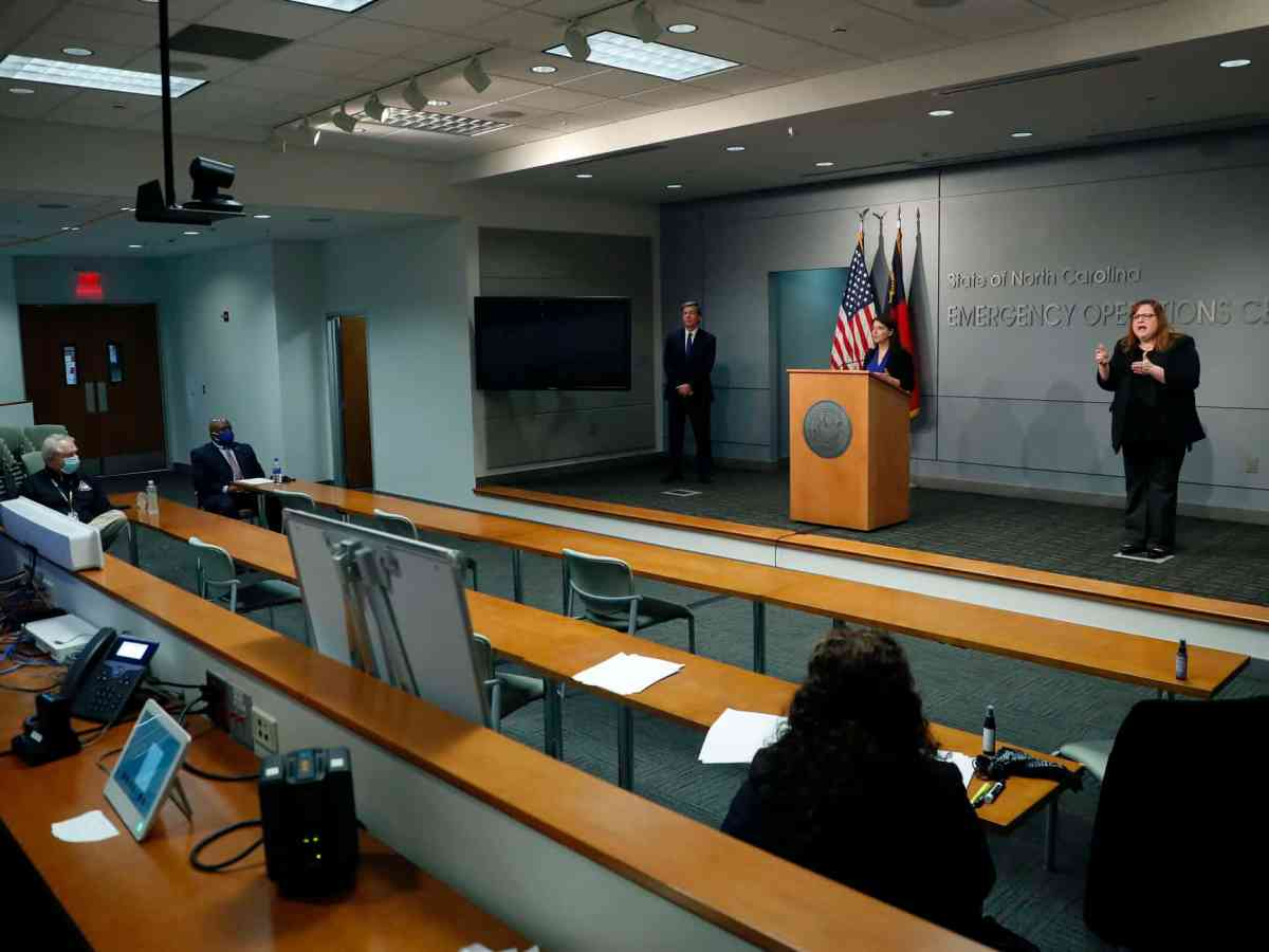 a woman at a podium speaks to a mostly empty room. the only others there are wearing masks, as they're social distancing because of COVID-19.