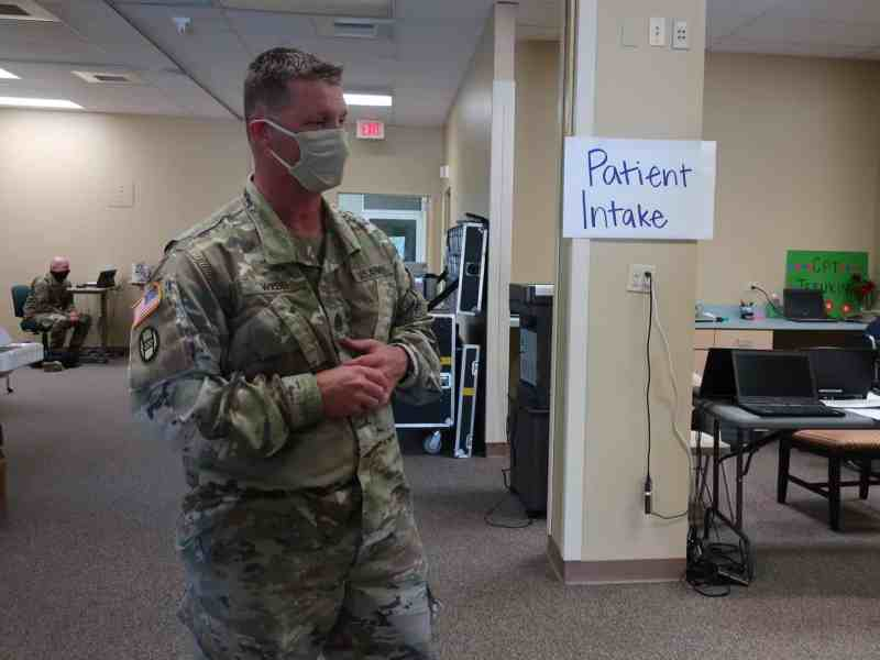 """man in fatigues and a face mask stands in front of a sign reading: """"patient intake"""" in a COVID-19 overflow centr"""