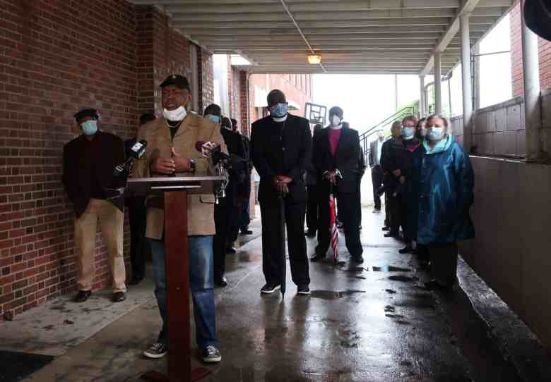 A group of people stand in the rain behind a podium, many wearing masks to prevent transmission of COVID-19